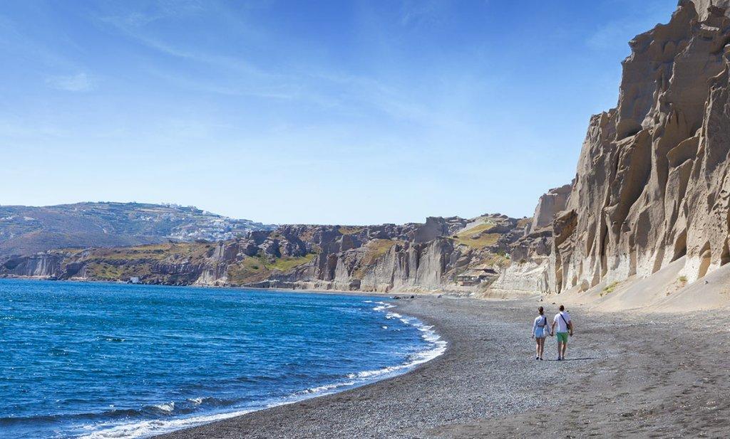 Casal em praia de Santorini