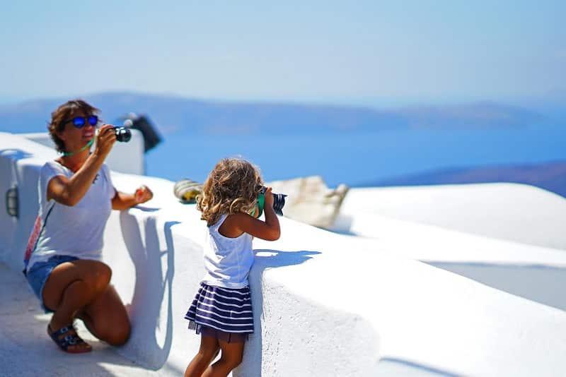 Criança tirando fotos em Santorini
